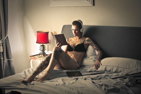 to undress: Girl reading in bed Stock Photo