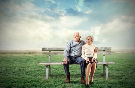 mujeres ancianas: Pareja de ancianos sentados en un banco