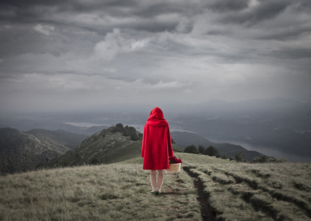 Little Red Riding Hood walking in a field Stok Fotoğraf