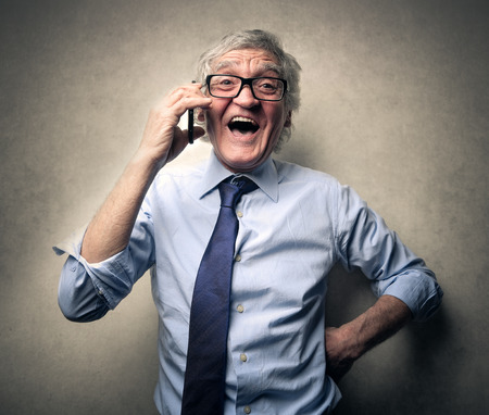 old man smiling: Businessman talking on the phone