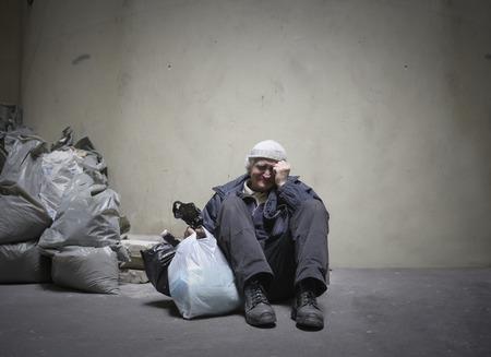 poor man: El hombre sin hogar que se sienta en el suelo