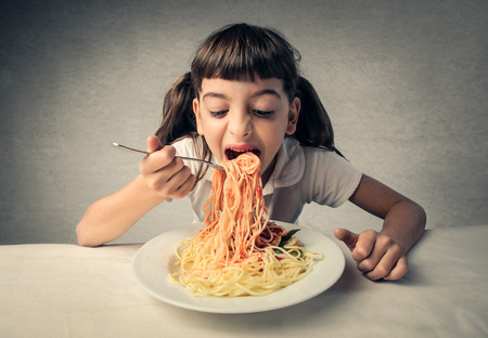 hungry kid: Young child eating pasta Stock Photo
