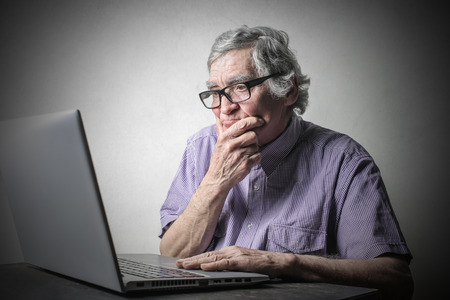 old pc: Doubtful man using a pc