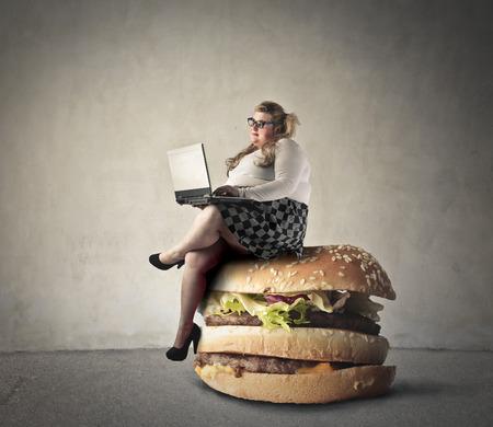 obeso: Mujer rechoncha que se sienta en una hamburguesa Foto de archivo