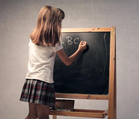 uniform skirt: Child writing on the blackboard