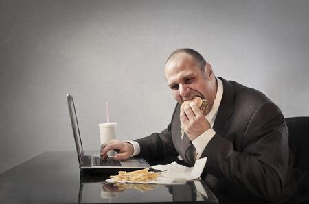 junky: Businessman eating junk food Stock Photo