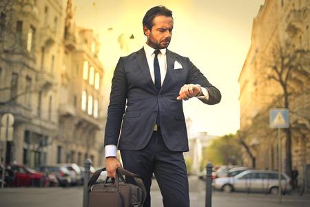 puntualidad: Elegantemente vestido hombre de negocios que controla el tiempo