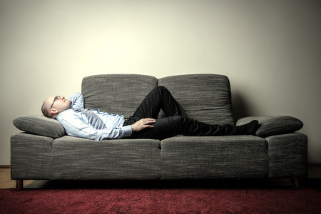 tired businessman: Tired businessman relaxing on the sofa