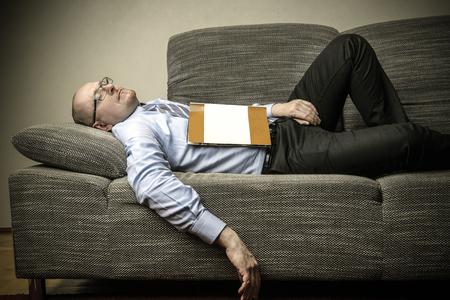 tired businessman: Tired businessman sleeping on the sofa Stock Photo