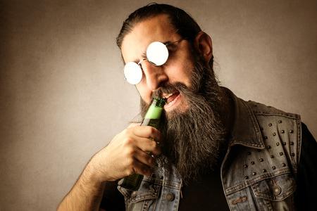 hombre tomando cerveza: El hombre tratando de abrir una botella de cerveza con los dientes Foto de archivo