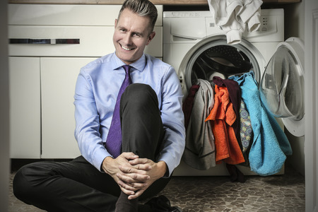 lavage: Businessman sitting next to the washing machine