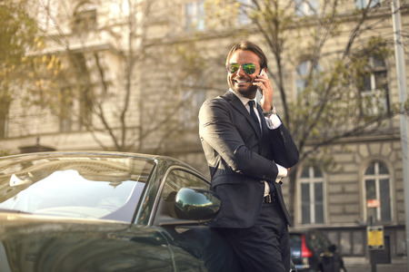 Successful businessman standing next to his posh car