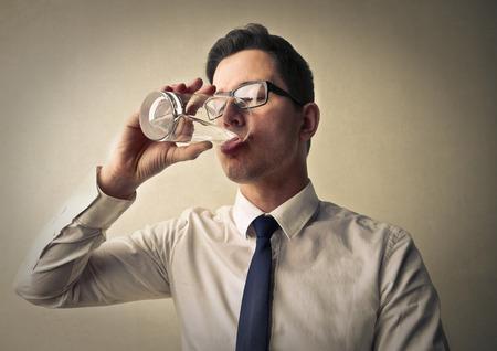 vasos de agua: El hombre de negocios de beber un vaso de agua Foto de archivo