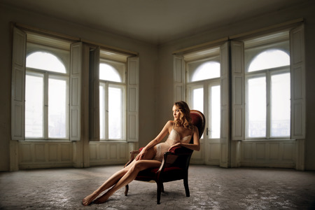 Woman sitting in a red chair in an empty room