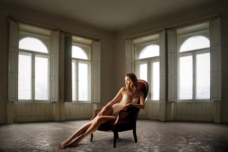 Vrouw zitten in een rode stoel in een lege kamer Stockfoto