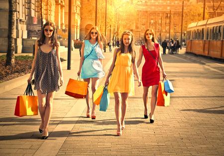 mode: Vier vrienden lopen in de straat Stockfoto
