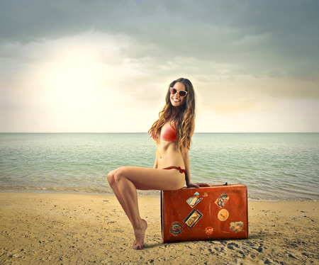 niñas en bikini: Joven mujer sentada en una maleta en la playa