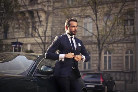그의 호화스러운 차 옆에 서있는 부유 한 남자