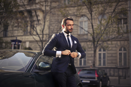 Rich man standing next to his posh car
