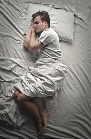 Jeune homme qui dormait dans son lit Banque d'images