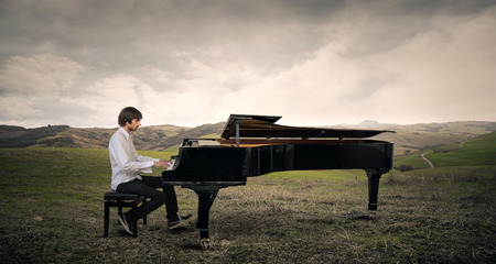 the silence of the world: Man playing the piano in a field