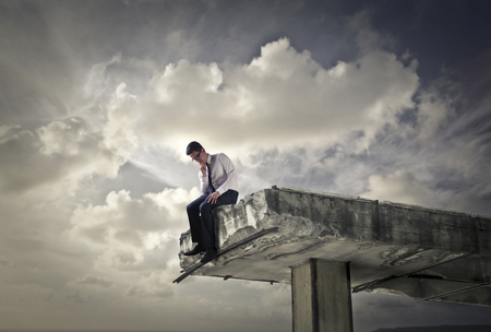 interruption: Businessman sitting on the edge of a broken bridge Stock Photo