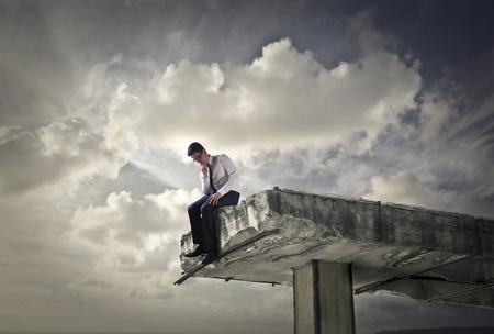 Zakenman zittend op de rand van een gebroken brug Stockfoto