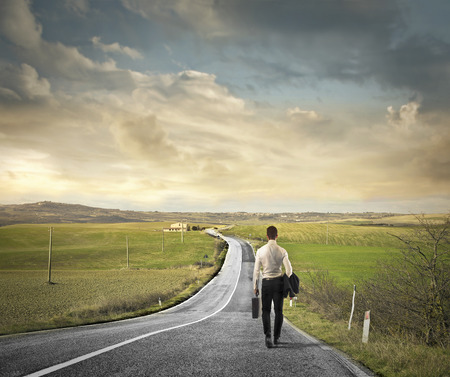 return trip: Businessman walking on a solitary road in the countryside Stock Photo
