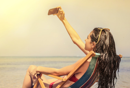 petite fille maillot de bain: Jeune femme faisant un selfie � la plage