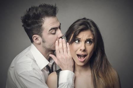 boyfriends: Man whispering secrets into a womans ear Stock Photo