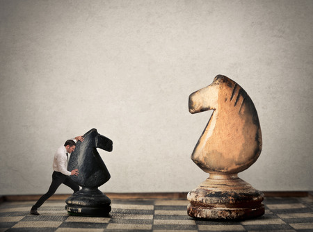 unequal: Lilliputian manager playing chess on a giant board