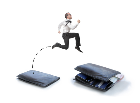 businessman jumping: Businessman jumping from a flat wallet to a full one