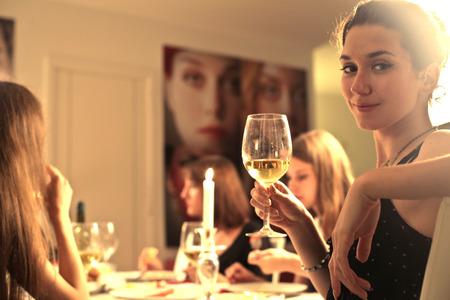 彼女の友達と夕食を食べている若い女性 写真素材