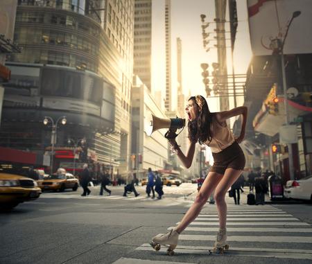 personas en la calle: Joven mujer de pie en una plaza gritando en un megáfono