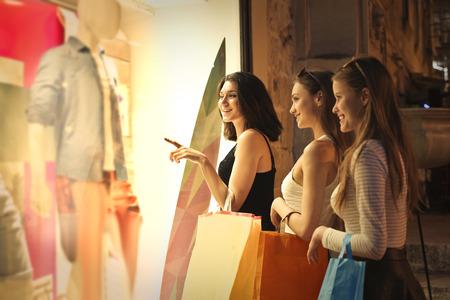 chicas de compras: Tres niñas mirando el escaparate de una tienda Foto de archivo