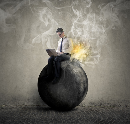 Geschäftsmann sitzt auf einer Bombe
