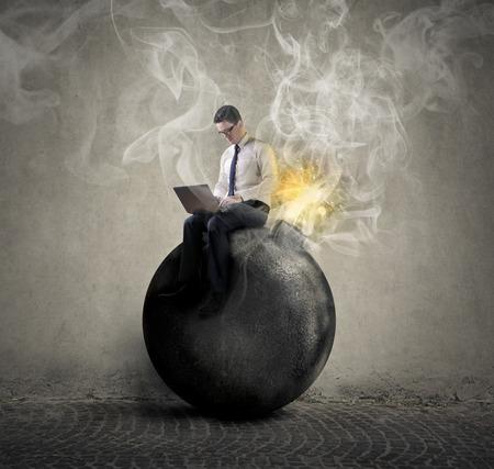 Hombre de negocios sentado sobre una bomba