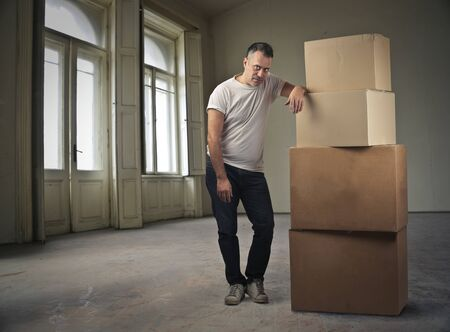 aside: Man standing aside some boxes