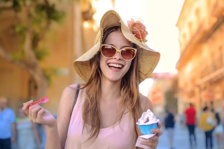 comiendo helado: Mujer sonriente que come el helado Foto de archivo