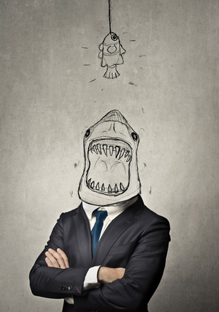 big fish: Businessman with a shark face eating a smaller fish Stock Photo