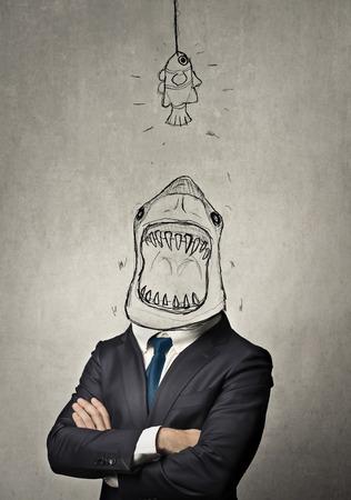 Geschäftsmann mit einem Hai Gesicht essen eine kleinere Fische Standard-Bild