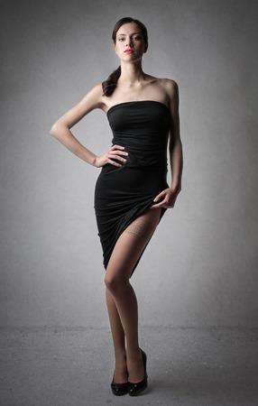 stockings woman: Beautiful woman wearing a black dress Stock Photo
