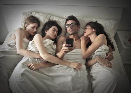 pareja en la cama: Hombre que duerme con tres mujeres Foto de archivo
