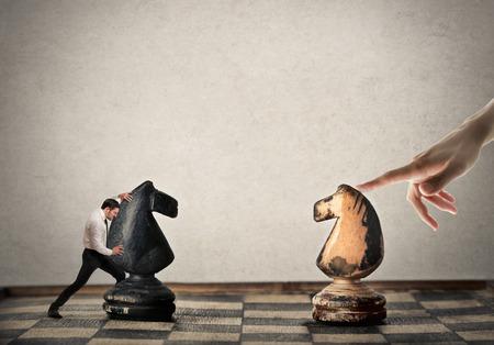 trabajando duro: Empresario jugar ajedrez contra un jugador desconocido Foto de archivo