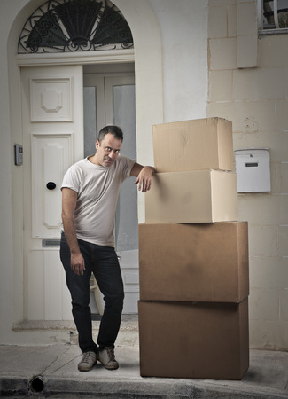 aside: Man standing aside a pile of boxes