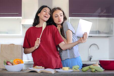 台所で料理を 2 人の友人