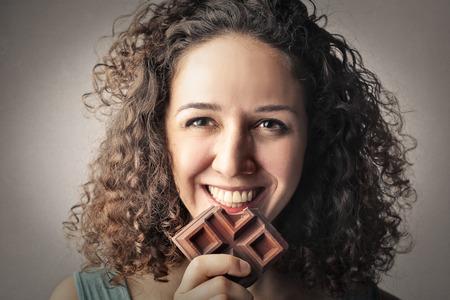 Glückliches junges Mädchen, das Schokolade isst