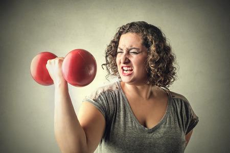 若い女性の持ち上がる重量 写真素材