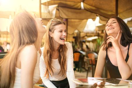 Drei Mädchen lacht, während auf einer Café-