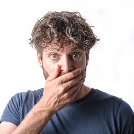 hand on mouth: Shocked man covering his mouth with one hand